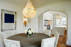 white beaded chandelier with round wood dining table on walk through dining room