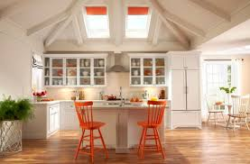 ... Airy white kitchen employs skylights with orange blinds along with  chairs in similar hue