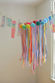 a collaborative chandelier with ribbons and pom poms made by kids