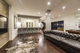 amazing basement featuring a long black leather chesterfield sofa paired with cowhide rugs placed in front of planked wall accented with flatscreen tv