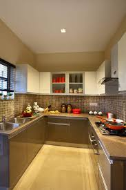 beige color modular kitchen with tiled wall and cabinets