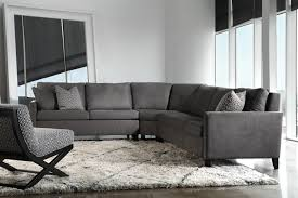 shaped grey velvet sectional sofa having back and arm also square furniture cushions with short black