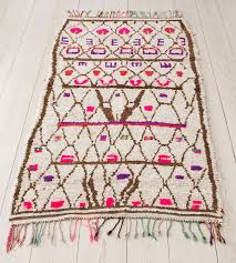 beautiful ourika rug with ivory background and pattern in brown pink and purple
