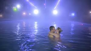 Couple Man And Woman Swimming In A Pool With Thermal Water At Night