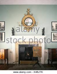 antique fireplace screen. antique girandole mirror above fireplace with an fire-screen in pale blue georgian dining screen