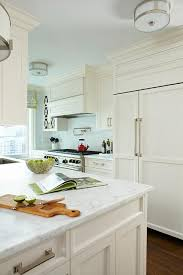 off white kitchen cabinets with white marble countertops and backsplash