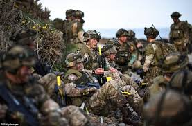 royal marines rest on the dundrennan beach as they wait for orders to move in
