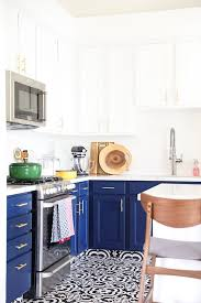 navy blue kitchen cabinets black and white tile floor and gold cabinet hardware