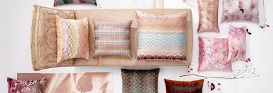 large multi colored patterned and sized pillows are neatly arranged on a chaise