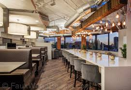 lighting beams. A Rustic Beam With Dripping Light Bulbs Beautifully Accents The Bar In This High-rise Lighting Beams