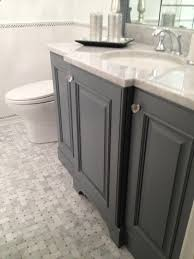 gray bathroom cabinets with crystal knobs and polished nickel faucet kit bathroom floor composed of marble basketweave tiles and subway tile baseboard