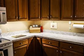 kitchen with wooden cabinets and using under cabinet lighting over marble countertops cabinet lighting kitchen