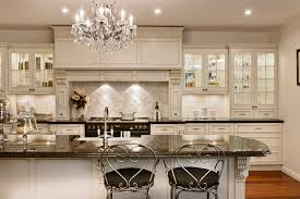 modern country kitchen decor with white ceramic backsplash and white wooden cabinet with glass door plus island with black glass top and chairs under