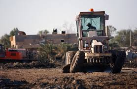 US Air Force (USAF) SENIOR AIRMAN (SRA) Byron Harper, 332nd Expeditionary  Civil Engineer Squadron (ECES), uses a John Deere 570 motor grader to  smooth out the gravel on a parking lot on Tallil Air Base (AB), Iraq during  Operation IRAQI ...