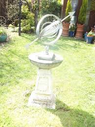 garden silver armillary sphere on solid sandstone base