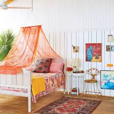 Sally's bed is along the white-paneled back wall of the cottage, under a
