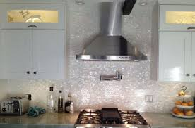 large stainless steel range hood gas stove stainless steel roaster tiny mother of pearl tile kitchen backsplash concrete countertop