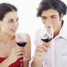 close up of a couple smelling the aroma of red wine