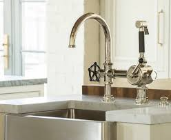 chrome wall mounted kitchen faucet with attached soap dish within