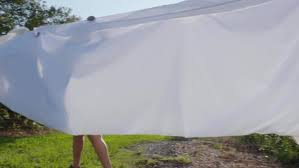 hanging sheet slow motion shot of a woman hanging a bed sheet on a clothesline
