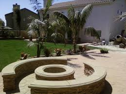 round fire pit with seat wall concrete cap and faux stone veneer design of affordable fire pits