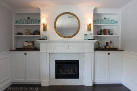 awesome white fireplace mantel with round mirror and wall lamps plus white cabinets also shelves for family room design