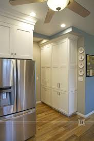 kitchen cabinets home office transitional: tall pantry white painted kitchen cabinets in a transitional style
