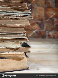 the edge of a stack of old books rebent on a wooden table close