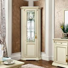 classic white polished corner tall display cabinet with glass door placed on hardwood floor the