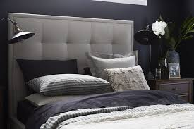 dark master bedroom with grey upholstered headboard and industrial bedside table lamps