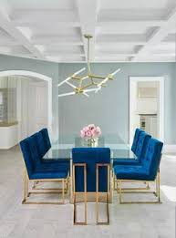 jonathan adler goldfinger blue velvet dining chairs frame a stunning long gl dining table with a