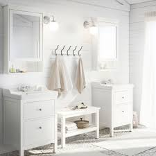 white bathroom cabinets. a white bathroom with two washbasins, bench, striped rugs and cabinets b
