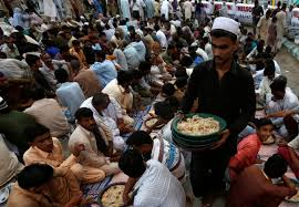 ramadan around the world newsweek middle east a volunteer distributes plates of boiled rice beef and potatoes to people gathering to break