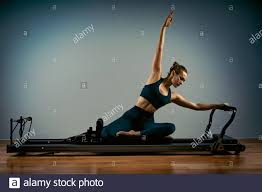 Light Pilates Yoga Studio Young Girl Doing Pilates Exercises With A Reformer Bed