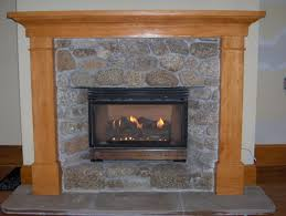 cushty black metal firebox in grey stone surround rustic wooden fireplace mantle to warm up your