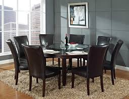 brown fur rug under the round dark brown wooden table plus dark brown leather chairs with