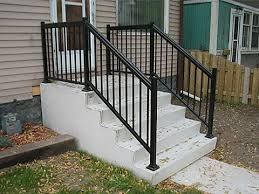 Intricately detailed iron railings garner attention without blocking incoming light or views of the arched window located behind this staircase. Home Depot Wrought Iron Step Railing Steps Parsons Precast Outdoor Stair Railing Railings Outdoor Porch Step Railing