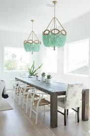 chic dining room features a gray dining table crate barrel big sur charcoal dining table lined with white wishbone dining chairs and white and gray