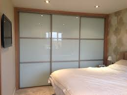 large white glass sliding closet doors with brown wooden bars and frame placed on the cream