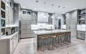 contemporary kitchen with light gray cabinets wood floors and white textured brown countertops