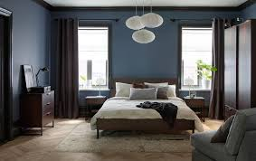 A large bedroom with a dark brown bed for two with bedlinen in beige and  grey