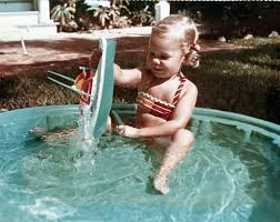 Florida Memory • Governor's daughter Claudia Kirk playing in pool at the  mansion.