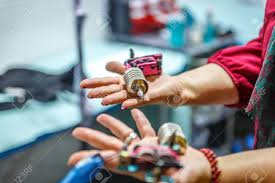 A Woman Has Two Tattoo Machines In Her Hands In A Little Studio