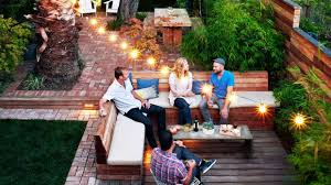 connect spacesweave together outdoor rooms by stringing cafe lights overhead between fence posts and trees