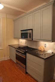 simple grey kitchen cabinet design with black granite top and beige wall