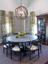 great dining room with round dining table and orb chandelier plus fabric curtain with cabinet