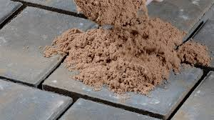 traditional masonry sand is swept into the paver joints to fill the joints and secure the pavers into place