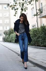 black pea coat is worn atop charcoal wool sweater tucked in high waisted shortened boot cut jeans