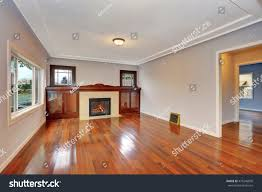 empty living room interior with polished hardwood floor fireplace with tile trim and cabinets
