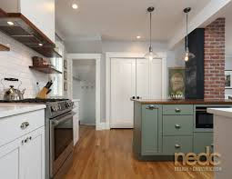 green cabinetry topped with a wooden countertop complements the brick wall original to this home